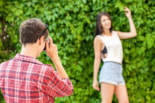 사진 작가는 녹색 벽 근처에서 아름다운 갈색 머리 모델을 촬영합니다. .