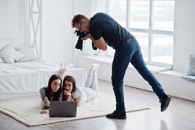 Photographer shooting on studio two twins models who are looking at the laptop. professional photographer on work. master class.