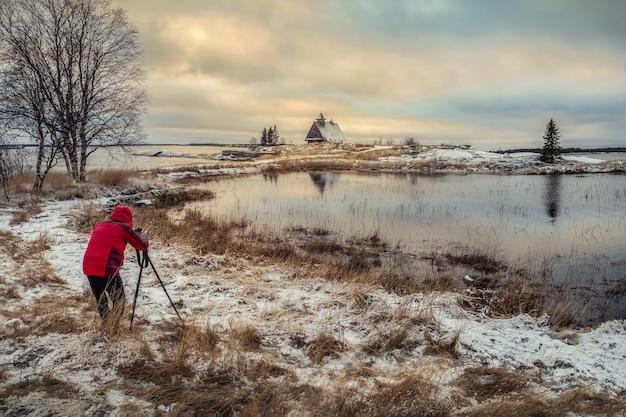 写真家は海岸に本物の家で素晴らしい夜明けの雪の冬の風景を撮影します。