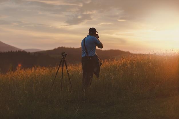 사진 작가는 산에서 일몰 풍경을 촬영