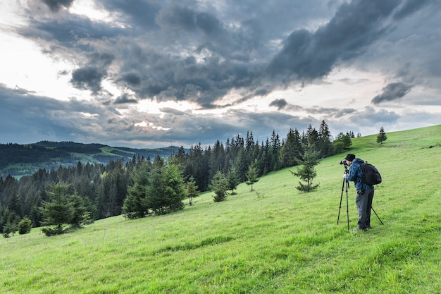 Photographer shoots mountain landscape with thunderstorm clouds in the evening