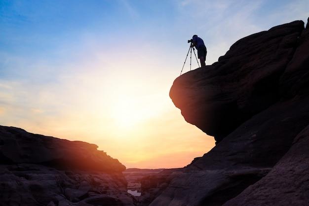 Фотограф стоять на вершине во время восхода солнца утром и фотографировать