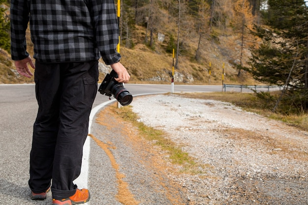 Photographer standing beside the road for looking his angle to take photo in bolzano ,italy.