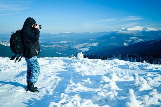 Фотограф стоял с камерой на холме с панорамным видом на зимнюю долину