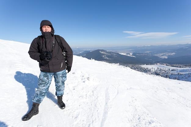 겨울 계곡의 파노라마 전망 언덕에 카메라와 함께 서 사진 작가