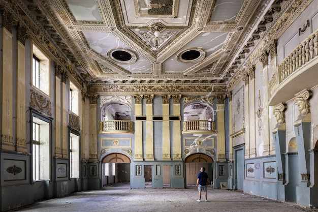 Photographer stands in an abandoned club hall in tbilisi, georgia