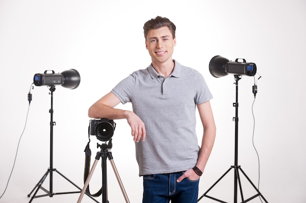 Photographer in studio. handsome young man in polo shirt leaning at the tripod with camera while standing in studio with lighting equipment on background