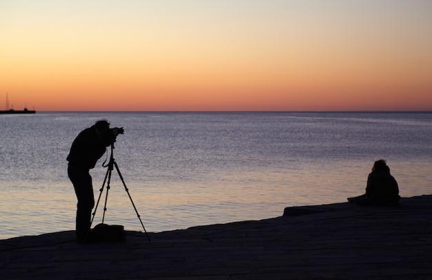 写真家は日没で写真を撮る