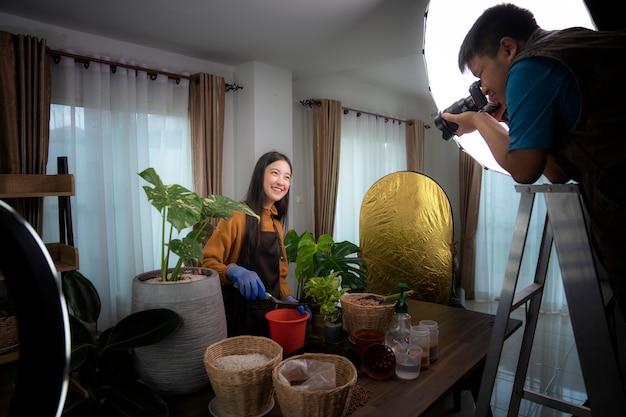 写真家は、アジアの女性モデルによって植物の概念を植えるために写真を撮る