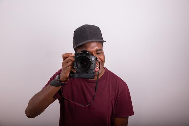 Фотограф делает снимок, глядя в видоискатель камеры. африканский фотограф, изолированные на белом фоне. фотография сделана в студии. концепция профессионального фотографа.
