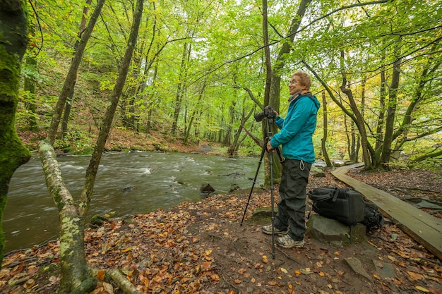 A photographer takes pictures of a beautiful view of the river and forest