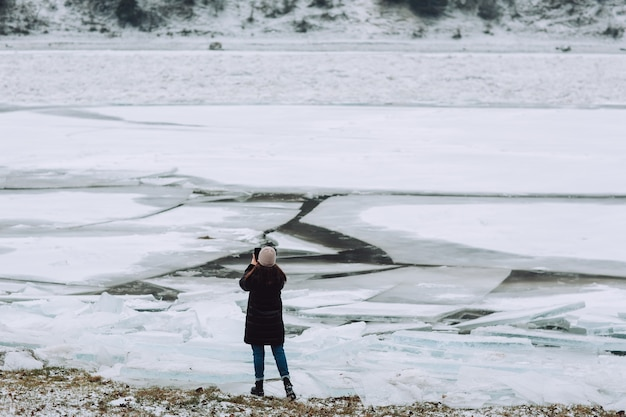 Photographer takes pictures frozen clear ice in winter river.