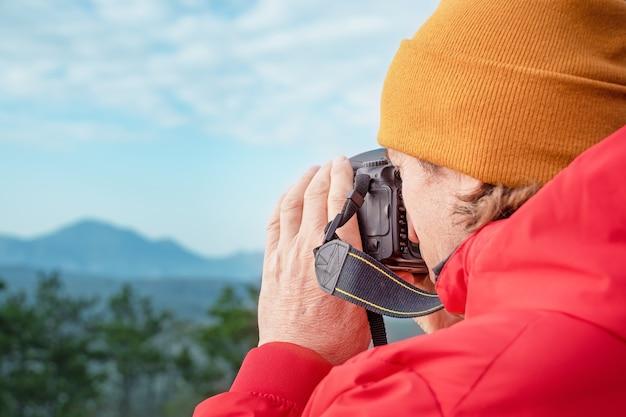 写真家は山で写真を撮ります