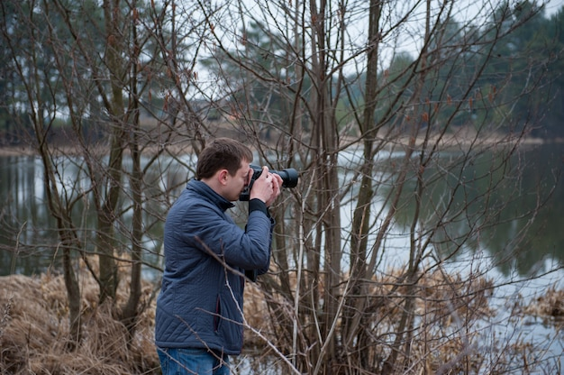 A photographer takes pictures of the landscape, an overcast photo of nature, a photographer at work