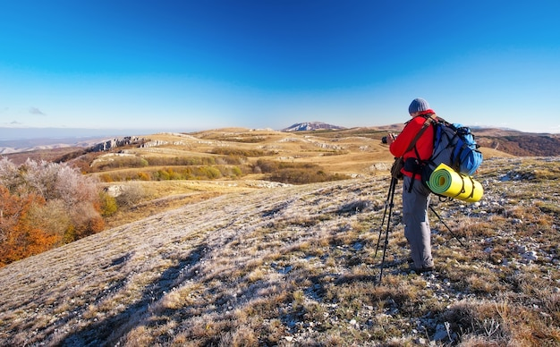 写真家は秋の山の頂上で写真を撮ります。山頂からの眺めを楽しむバックパックを持った旅行者