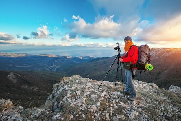 写真家は秋の山の頂上で写真を撮ります