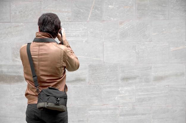 Фотограф принимает выстрел из кирпичной стены