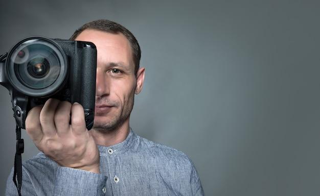 Фотограф делает снимок на цифровой зеркальный фотоаппарат с объективом 85 мм. кавказский мужчина фотографирует вас с зеркальной камерой. фотограф с объективом в руке на сером фоне. камера крупным планом. сосредоточиться на глазу