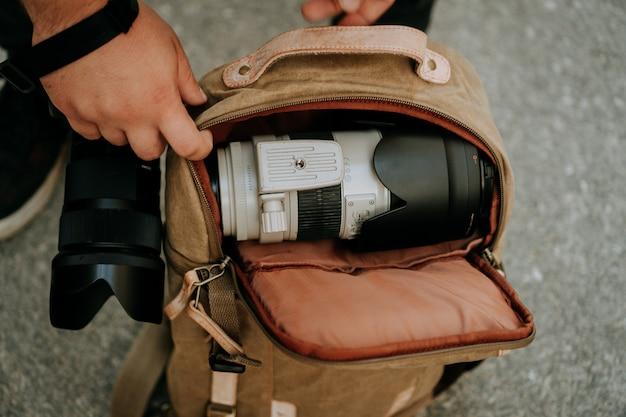 カメラバッグから白いカメラレンズを取り出す写真家