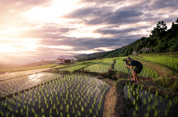 夕焼けと夕暮れの空の中に田んぼで写真を撮る写真家