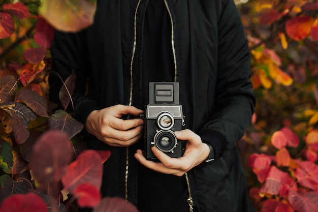 Photographer taking photo with retro camera with colorful red leaves