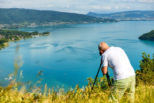 Photographer taking a picture at annecy lake, france