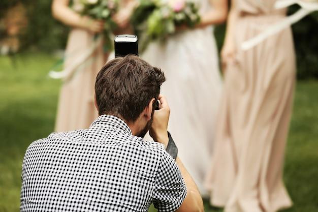 Фотограф фотографирует невесту с подружками невесты