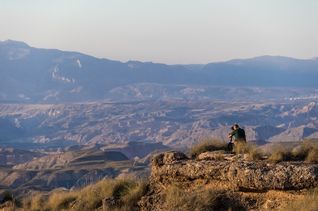 A photographer taking pictures of the gorafe desert in the light of sunset