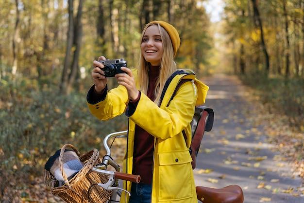 Фотограф, делающий снимки в осеннем лесу, концепция путешествия здорового образа жизни