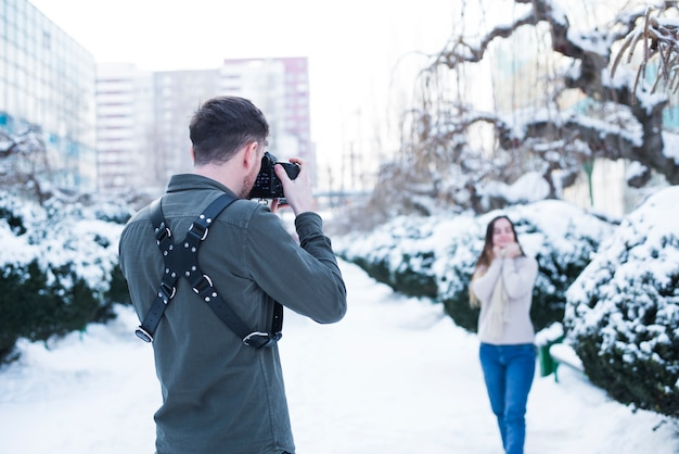 Photographer taking pictures of model in snowy street