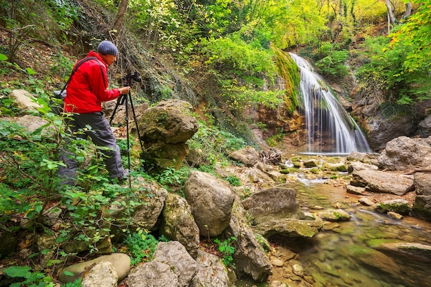 The photographer taking pictures of mountain landscape with a waterfall in autumn