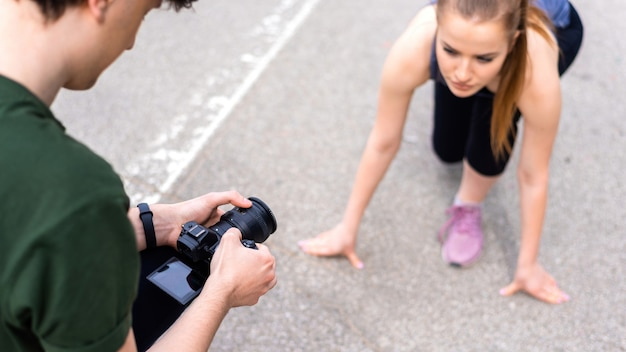 Photographer taking shot of a young blonde woman in sportswear preparing to start running at outdoors training, road