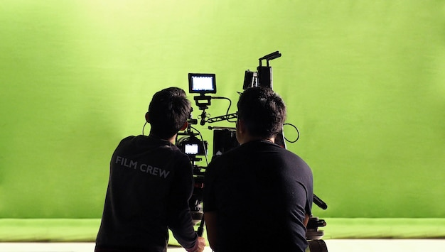 Photographer team and film crew and high definition online video camera and green chroma key for make movie shooting in big studio.