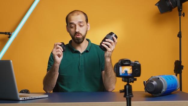 브이로그 에피소드를 녹화하는 동안 사진가가 카메라 렌즈를 테스트하고 있습니다. 카메라 렌즈 기술 디지털 녹화 소셜 미디어 인플루언서 콘텐츠 제작자, 팟캐스트, 브이로깅 및 블로깅을 위한 전문 스튜디오