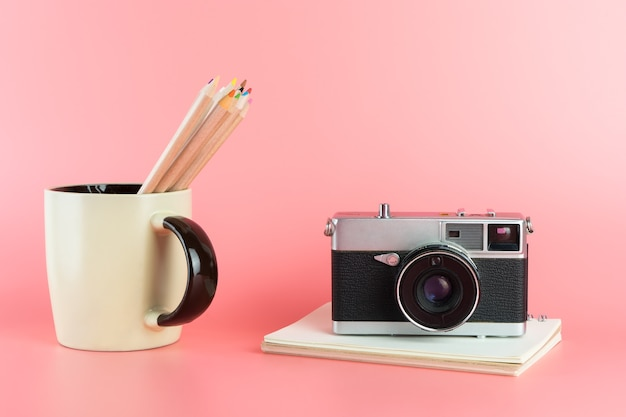 Photographer tools with vintage camera and color pencils
