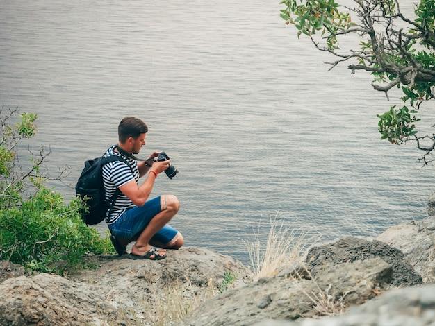 Photographer tourist man looking at the screen digital slr professional camera
