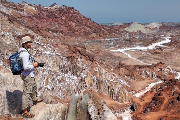 Hormuz island, hormozgan, iran의 짠 산을 걸어서 캠핑하는 사진 작가 여행자.