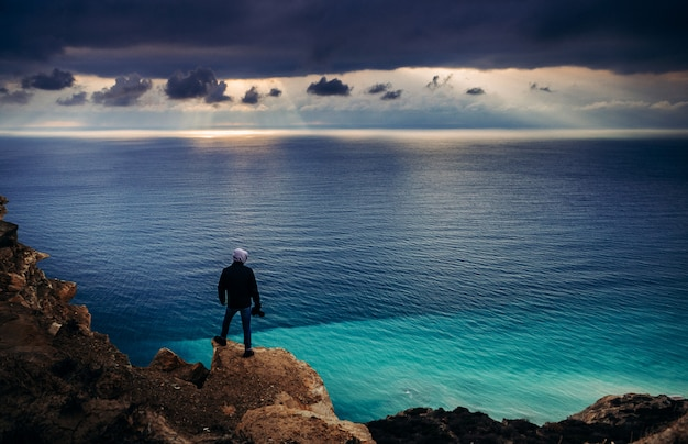 Photographer traveler stands on the edge of a cliff above the turquoise sea at sunset