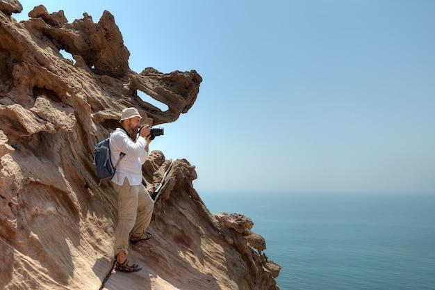 사진 작가 여행자는이란 hormoz의 바위에 선다.