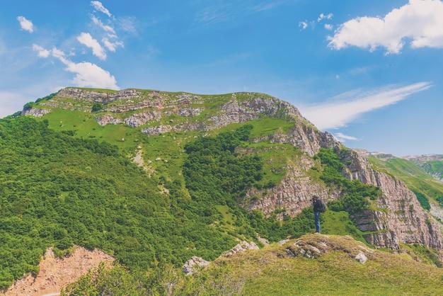 山でカメラとバックパックを持った写真家旅行者