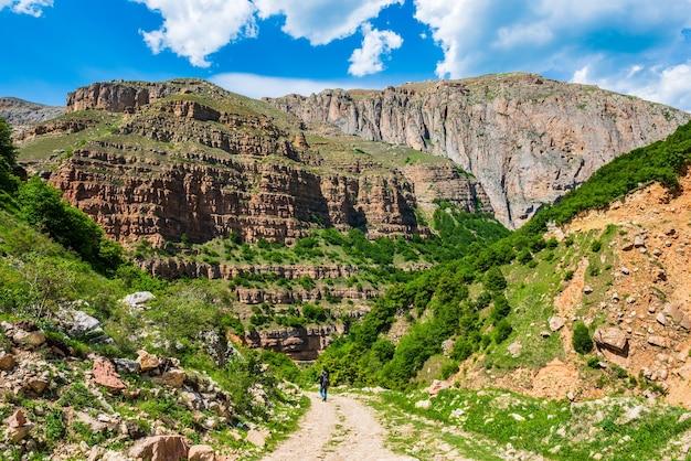 山の未舗装の道路を歩くカメラとバックパックを持つ写真家の旅行者