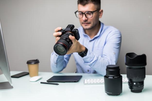 Фотограф загружает фотографии со своей камеры на компьютер в офисе