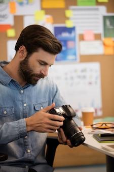 Фотограф с помощью камеры в творческом офисе