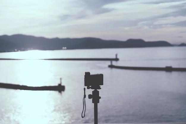 Фотограф, использующий компактную камеру для съемки заката на острове