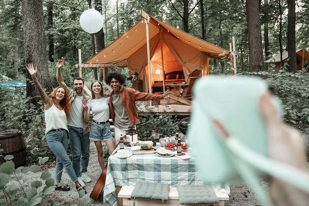 Photographer view of making polaroid photo of friends on picnic, camping glamping life, resting with diverse friends outdoors, enjoying summer camping trip, having fun time in forest, copy space