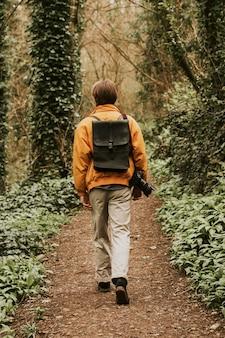 Фотограф гуляет по лесу сзади