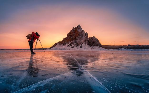写真家は赤い服を着て、ロシアのシベリアのバイカル湖の凍った水の中の氷を自然に砕いて日の出のシャーマンカ岩の写真を撮ります。
