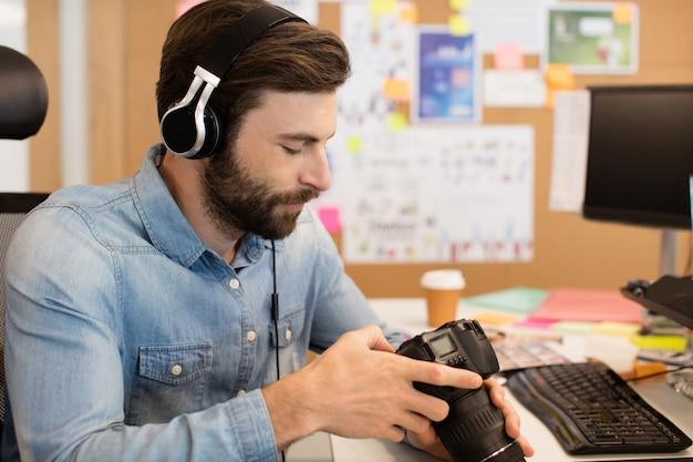 창의적인 사무실에서 카메라를 사용하는 동안 헤드폰을 착용하는 사진 작가