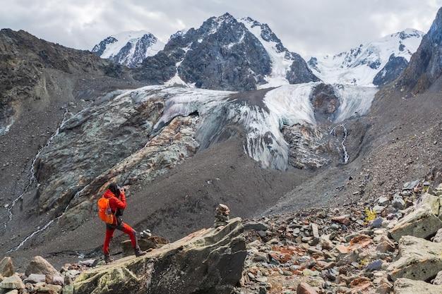 Фотограф с рюкзаком на краю обрыва. опасные горы и бездна. потрясающий вид на горную долину под голубым ледником.