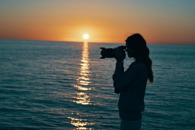海の近くの夕暮れ時にカメラを持つ写真家